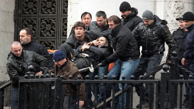 Bodyguards carry Zlatomir Ivanov, after he was shot in front of central court house in downtown Sofia, Tuesday.