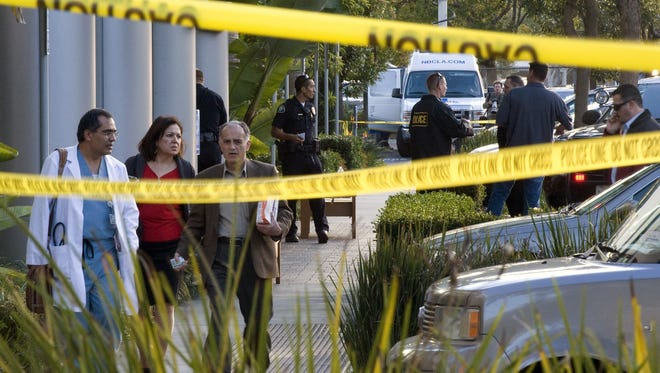 Police investigate as medical personnel exit the scene outside a medical office where a doctor was fatally shot Jan. 28 in Newport Beach, Calif.