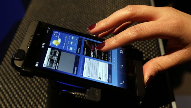 A woman uses a new touchscreen BlackBerry Z10 smartphone.