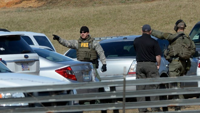 Law enforcement officials continue to work the scene of an ongoing hostage crisis in Midland City, Ala., Friday, Feb. 1, 2013.