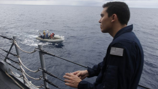 A U.S. Coast Guard officer watches as a RHIB boat returns to the USS Underwood after participating in drug interdiction training exercises while patrolling in international waters near Panama.