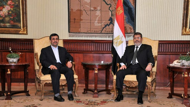 Iran's President Mahmoud Ahmadinejad, left, and Egyptian President Mohammed Morsi pose for photographers in Cairo on Feb. 5.