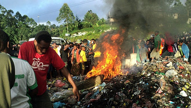 Bystanders watch as a woman accused of witchcraft is burned alive in the Western Highlands provincial capital of Mount Hagen in Papua New Guinea.