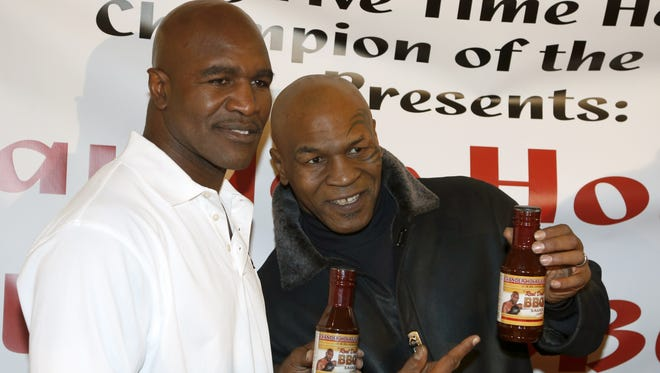 Former heavyweight champions Mike Tyson, right, and Evander Holyfield during a promotional event for Holyfield's Real Deal barbecue sauce at a Chicago grocery store.