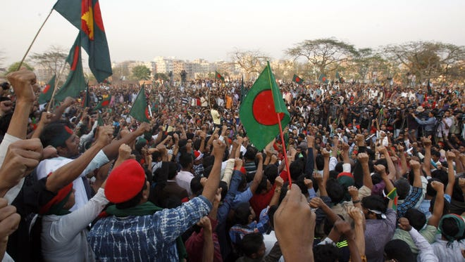 Bangladeshis wave flags and shout slogans demanding death to Islamic political party leaders who are on trial for alleged war crimes during the country's 1971 independence war, in Dhaka, Bangladesh, Saturday.