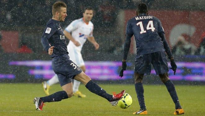 Paris Saint Germain's David Beckham, left,  runs with the ball  during the League One match in Paris Sunday. Beckham made his PSG  debut.