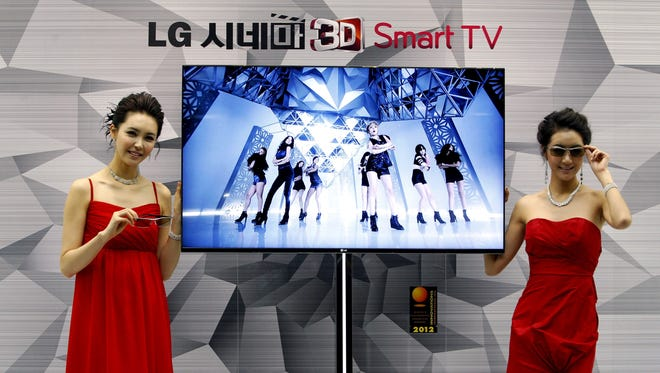 In this file photo, South Korean models pose with a CINEMA 3D Smart TV.