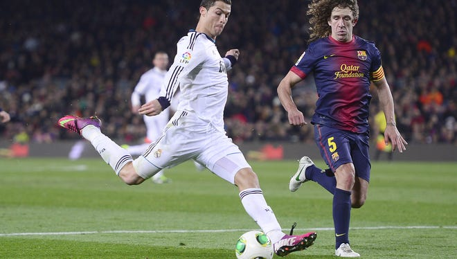 Real Madrid's Cristiano Ronaldo, left, and Barcelona's Carles Puyol challenge for the ball during a Copa del Rey soccer match between FC Barcelona and Real Madrid in Barcelona Tuesday.