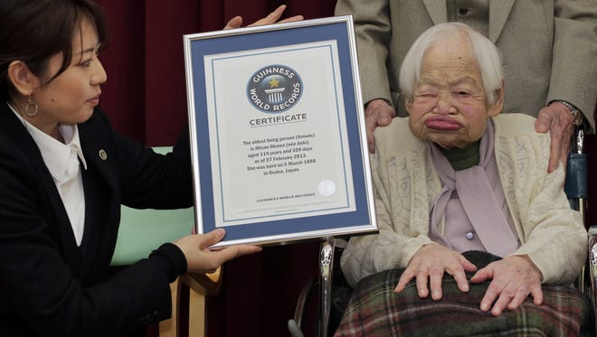 Japan's 114-year-old Misao Okawa, right, poses with the certificate of the world's oldest living woman, which was presented to her by Guinness World Records Japan Country Manager Erika Ogawa, right, at a nursing home in Osaka, western Japan.