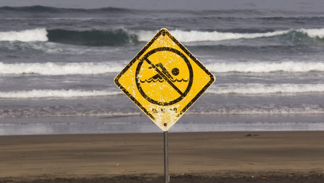 A no swimming sign is displayed at Muriwai Beach near Auckland, New Zealand, on Feb. 28, a day after Adam Strange was killed by a shark.