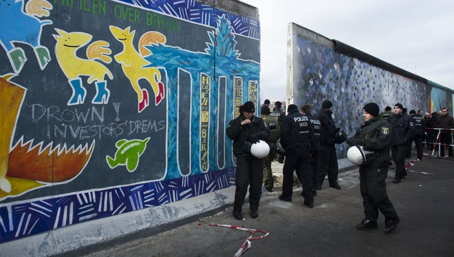German police officers protect a part of the former Berlin Wall in Berlin, Germany, on Friday.