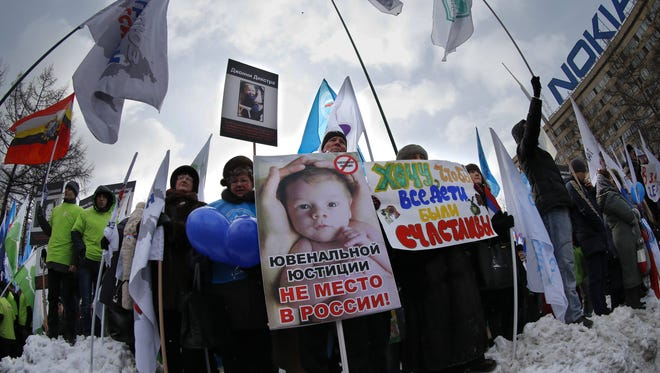 "Demonstrators hold posters reading ""There is no place for juvenile justice in Russia,"" ""I want all children be happy"" during a massive rally to back the ban on U.S. adoptions of Russian children in Moscow,  on Saturday."