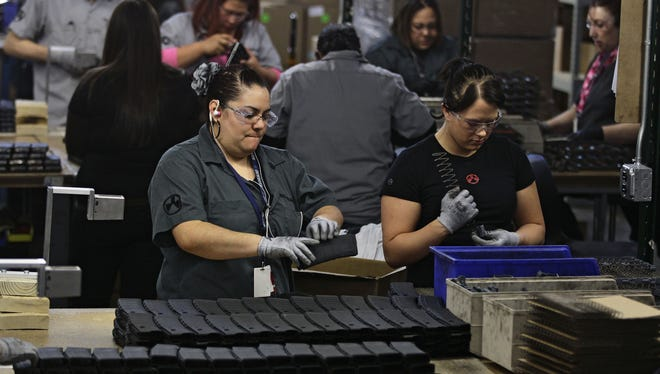 In this photo from Thursday, workers assemble 30-round capacity ammunition magazines for high-velocity rifles, inside the Magpul Industries plant in Erie, Colo.