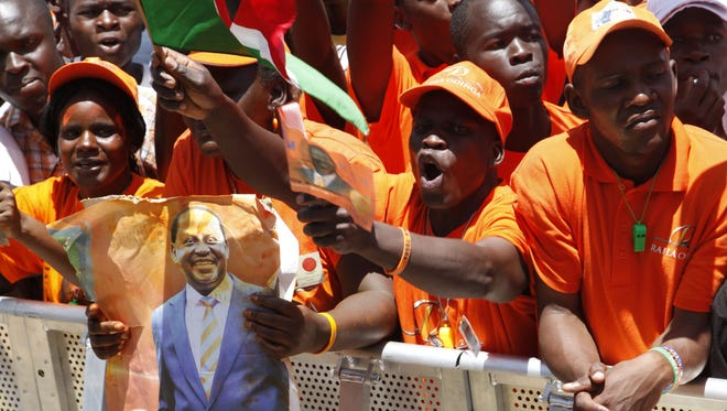 Supporters of Kenyan Prime Minister and Presidential candidate, Raila Odinga, holding his photo and the Kenyan flag wait at Nyayo National Stadium, Nairobi, Kenya, on Saturday, the final day of the campaign for the election.