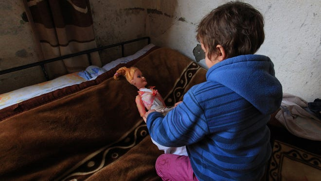 Marsela, 9, plays with her doll, in a photo from Jan. 18, 2013. She is the child of a blood feud family.