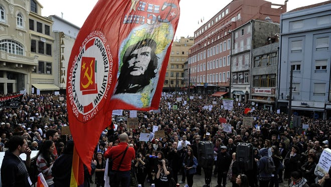 """A flag depicting Ernesto """"Che"""" Guevara it's hold over a demonstration against austerity measures applied by the bailed-out Portugal's government on Saturday in Porto, Portugal."""