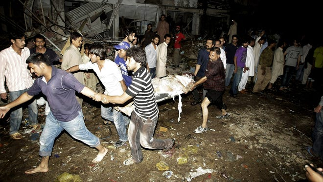 Pakistani men carry the body of a man from the site of a bomb blast in Karachi, Pakistan, on Sunday.