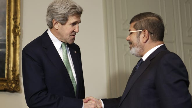 U.S. Secretary of State John Kerry, left, shakes hands with Egyptian President Mohammed Morsi at the Presidential Palace in Cairo on Sunday.