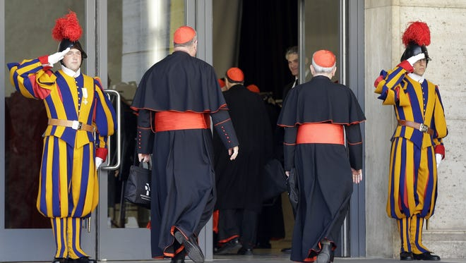 Vatican Swiss guards salute as cardinals arrive for a meeting at the Vatican on Monday.