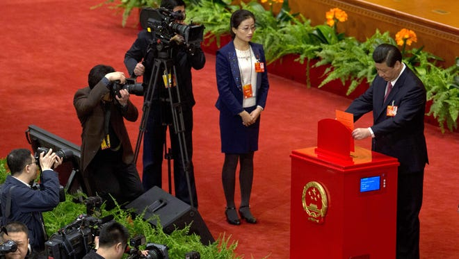 Chinese Communist Party chief and incoming-President Xi Jinping casts his vote at a plenary session of the National People's Congress in Beijing on Thursday.
