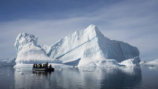 In this Dec. 1, 2009 photo provided by Aurora Expeditions, an inflatable boat carries tourists past an iceberg along the Antarctic Peninsula.