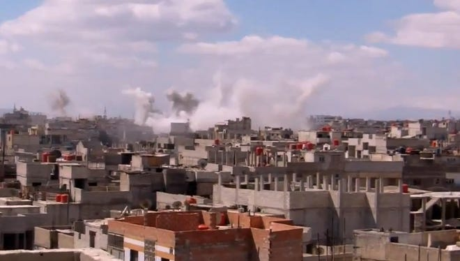 Columns of smoke rise from heavy bombing by Syrian government forces in Arbeen, Syria, on March 18
