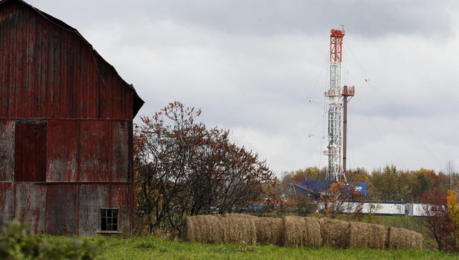 In this Oct. 14, 2011, file photo, a drilling rig is set up near a barn in Springville, Pa., to tap gas from the giant Marcellus Shale gas field.