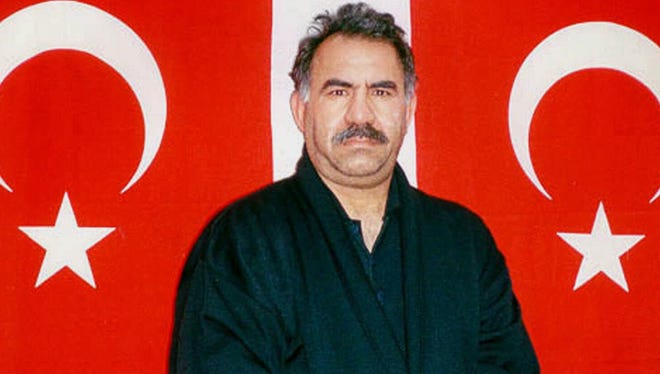 Kurdish rebel leader Abdullah Ocalan poses in front of Turkish flags before being interrogated by Turkish officials in 1999.