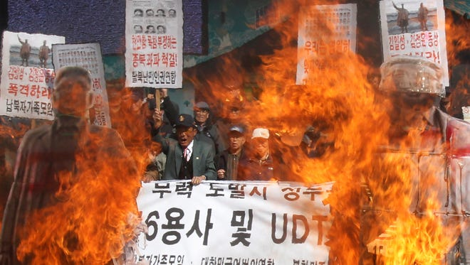South Korean conservative activists burn cutout pictures of North Korean leaders.