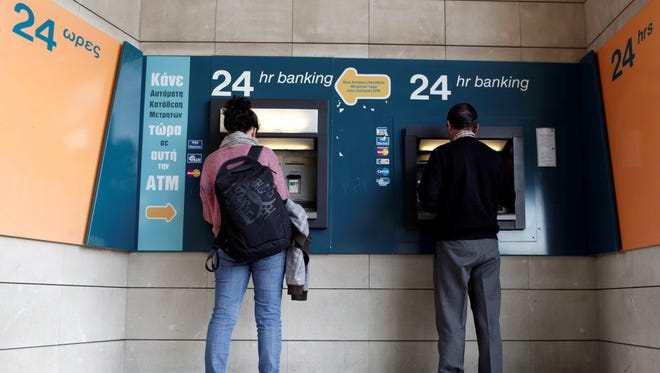 People use ATMs outside a closed branch of the Bank of Cyprus in capital Nicosia, Cyprus, on March 27, 2013