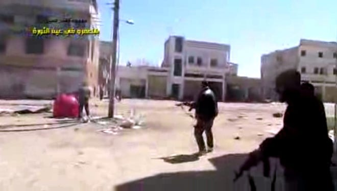 Syrian rebels battle with regime forces in Homs, Syria, on March 26.