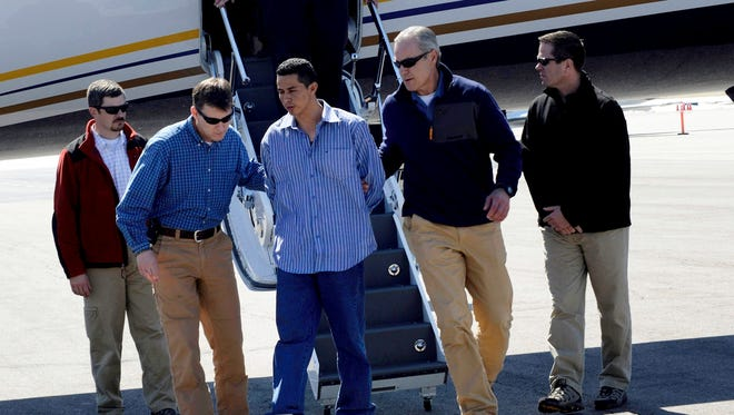 Denver Special Agents escort Edwin Ernesto Rivera Gracias off a plane on Wednesday in Denver.