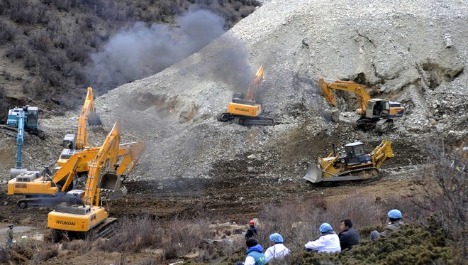 In this photo released by China's Xinhua News Agency, earthmovers remove rocks and mud on the scene where a landslide hit a mining area in Maizhokunggar County of Lhasa, southwest China's Tibet Autonomous Region, on Friday.