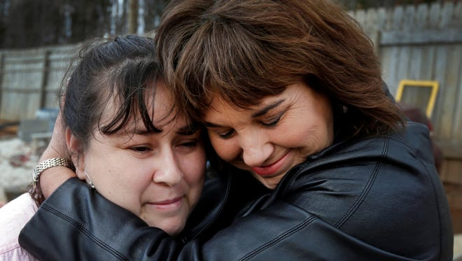 Victims of the ZeekRewards Ponzi scheme: Sarah Chavez, left, is embraced by Caron Myers at her home in Lexington, N.C.