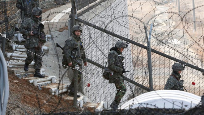 South Korean soldiers patrol along a barbed-wire fence near the border village of Panmunjom in Paju, South Korea, on March 31.
