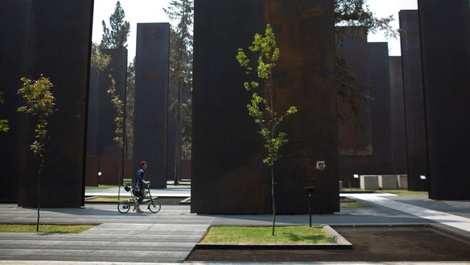 A visitor pushes a bike through a memorial to victims of violence on the day of its unveiling in Mexico City, Friday.