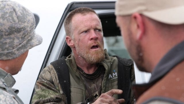 This image provided by the Emery County Sheriff's Office shows detectives placing fugitive Troy James Knapp into custody Tuesday in mountains outside of Ferron in central Utah. Authorities captured the elusive survivalist on Tuesday who is suspected of burglarizing Utah cabins and leaving some covered with threats and bullet holes — ending a saga that began six years ago. (AP Photo/Emery County Sheriff's Office)