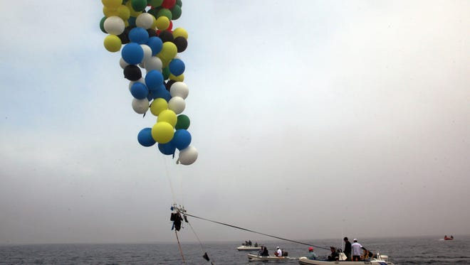 South African cluster balloonist Matt Silver-Vallance in mid air en route from Robben Island to the mainland near Cape Town, South Africa on Saturday.