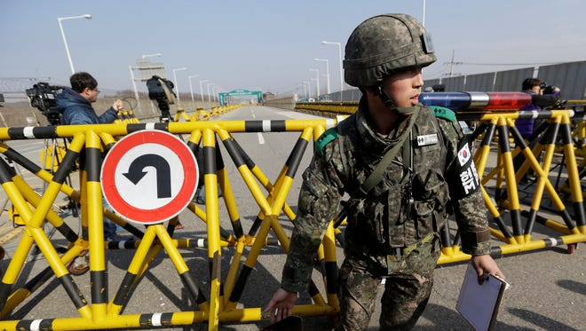 A South Korean army soldier moves a part of barricade for the media to enter at Unification Bridge near the border village of Panmunjom, that has separated the two Koreas since the Korean War.