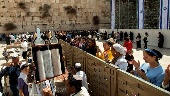 A man holds up a Torah scroll as women stand across a fence at the Western Wall, the holiest site where Jews can pray in Jerusalem's old city.