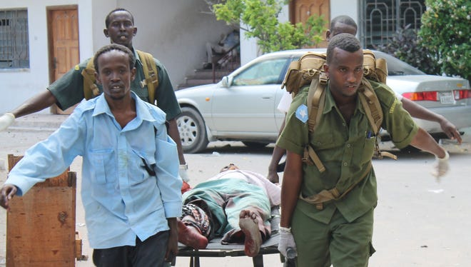 Somali soldiers carry a wounded civilian from the entrance of Mogadishu's court complex during a siege by militants in Mogadishu, Somalia, on Sunday.