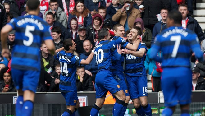 Manchester United's Michael Carrick celebrates with teammates after scoring against Stoke during their English Premier League soccer match.