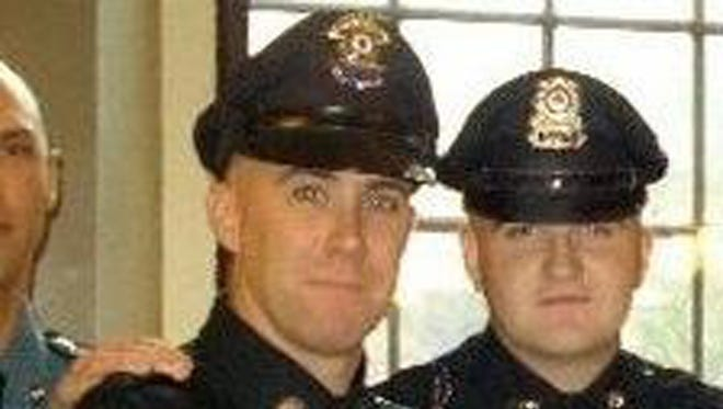 In this 2010 photo, Richard Donohue, left, and Sean Collier pose together for a photo at their graduation from the Municipal Police Officers' Academy.