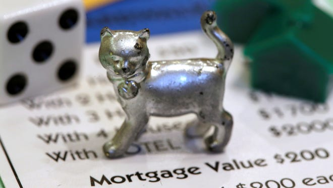 The newest Monopoly token, a cat, rests on a Boardwalk deed next to a die and houses at Hasbro headquarters, in Pawtucket, R.I.