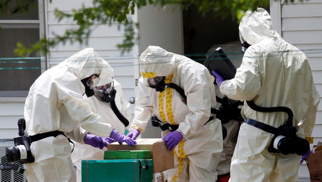Federal agents wearing hazardous material suits and breathing apparatus inspect the home and possessions in the West Hills Subdivision house of Paul Kevin Curtis in Corinth, Miss.