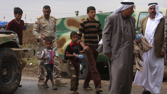 Iraqi army soldiers escort young and elderly people leaving a protest site in Hawija, Iraq, April 22, 2013.