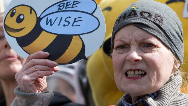 British fashion designer Vivienne Westwood holds up a sign supporting beekeepers as she joins a demonstration in London on Friday.