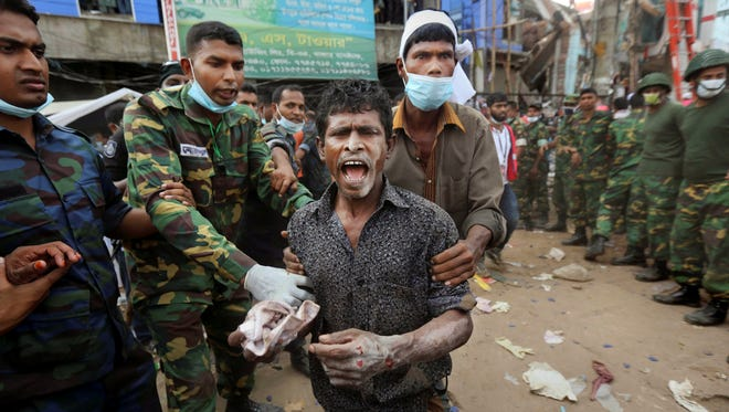 A Bangladeshi garment worker who soldiers said was pulled alive Friday from the rubble reacts as he walks on his own at the site of a building that collapsed Wednesday in Savar, near Dhaka, Bangladesh.