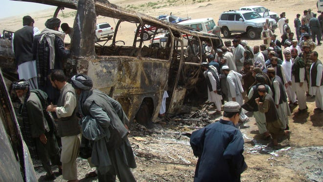 Afghan men surround a burned bus Friday in Maiwand district, on the highway between Kandahar and Helmand, Afghanistan.