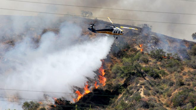 A Los Angeles County Fire Department helicopter drops water on a fire burning on the foothills of the San Gabriel Mountains in Monrovia, Calif., last weekend. Authorities say California is facing a dangerous wildfire season due to a dry winter that has left the normally green hills of spring parched and tinder-dry.